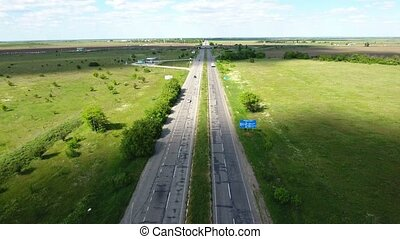 Aerial shot of a country highway with cars and green agricultural fields nearby