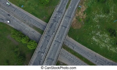 Aerial shot of a countryside intersection with moving trucks in a sunny day