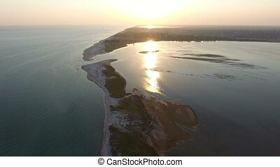 Aerial shot of a curvy and narrow Dzharylhach island sand spit at sunset