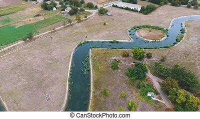 Aerial shot of a curvy canal with a tiny islet running thru...