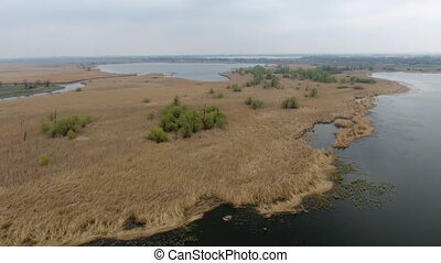 Aerial shot of a curvy river hook with rugged coastline and straw looking grass