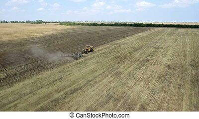 Aerial shot of a dusty field and a farm tractor pulling a...