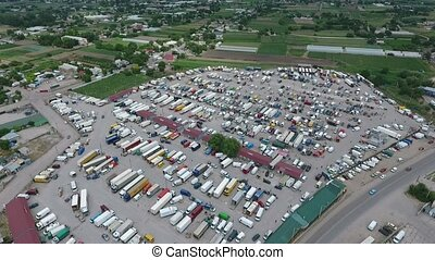 Aerial shot of a farmers` market with kiosks, autos and trailers in autumn