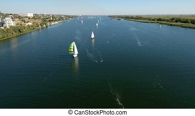 Aerial shot of a fine looking white yacht sailing in the Dnipro dark blue waters