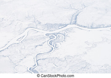 Aerial shot of a frozen river possibly the Olenyok River in northern Siberia in the foot hills of the Verkhoyansk Mountains, May. Note there are several ox bows cut off from the river.