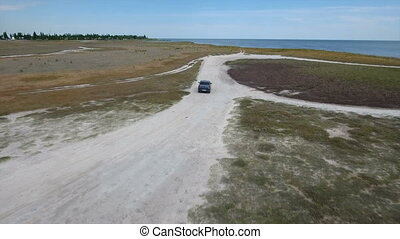 Aerial shot of a green car dashing along the sand road at the Black Sea
