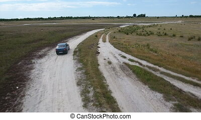 Aerial shot of a green car going along the country road at...