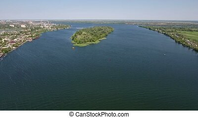 Aerial shot of a green island on the Dnipro river in a sunny day in summer