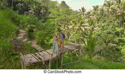 Aerial shot of a happy family tourists visiting famous Tegalalang Rice Terraces in Ubud village on the Bali island