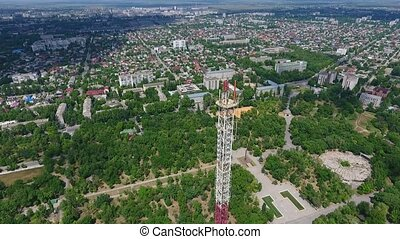 Aerial shot of a high television tower hovering in the city...