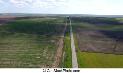Aerial shot of a highway and a road going along some fine...