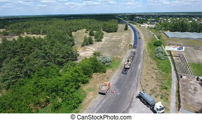 Aerial shot of a highway blacktopping and repairing on a sunny day in summer