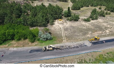 Aerial shot of a highway blacktopping, excavating, and repairing in summer