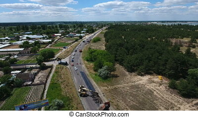 Aerial shot of a highway repairing, blacktopping, excavating, in summer