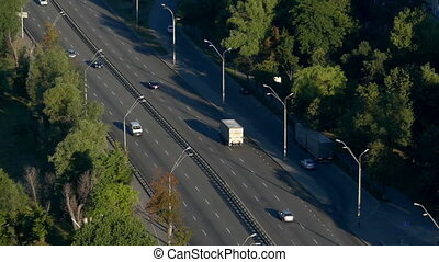 Aerial shot of a highway with greenery and lamposts in summer