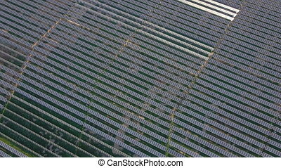 Aerial shot of a huge solar power plant in a big field. ...