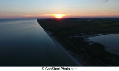 Aerial shot of a  huge white sun at sunset over an island in the Black Sea