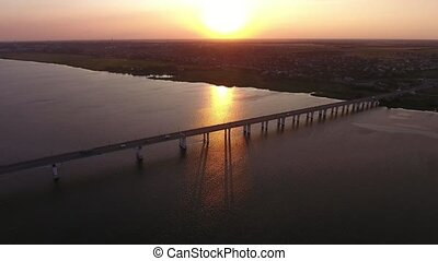 Aerial shot of a lengthy bridge at splendid sunset from a...