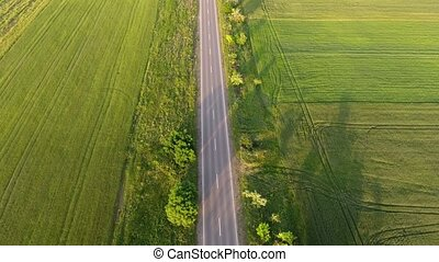 Aerial shot of a lengthy highway rushing among green meadows...