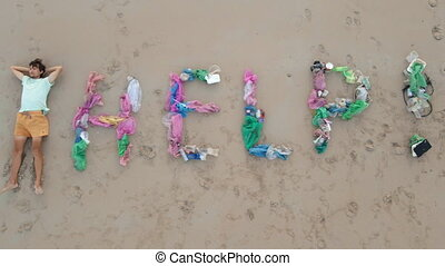 Aerial shot of a lettering HELP made of trash on a sandy beach. A sad man ecological volunteer is laying on the sand by the lettering. Stop plastic pollution.