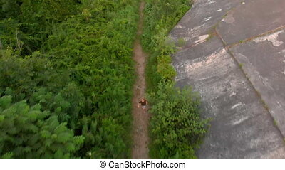 Aerial shot of a little boy running at the territory of an...
