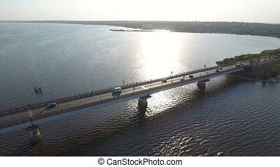 A wonderful bird`s eye view of a long modern bridge over the Southern Bug with a lot of moving cars and trucks on a sunny day in summer. The skyscape is gorgeous. The riverbank is dark green