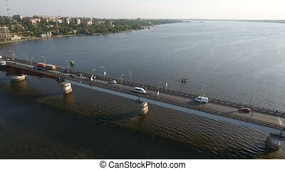 Aerial shot of a long concrete bridge over the Southern Bug at sunset