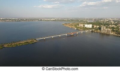 Aerial shot of a long modern bridge over the Dnipro on a sunny day in summer