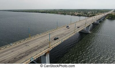Aerial shot of a long modern bridge over the Dnipro with heavy traffic  in summer