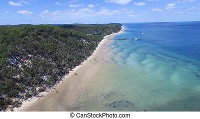 Aerial shot of a long shoreline and blue ocean