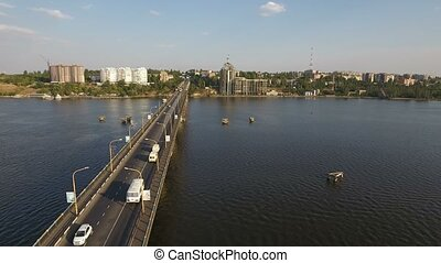 A gorgeous bird`s eye view of a long modern bridge over the Southern Bug with a lot of moving cars and trucks on a sunny day in summer. The skyscape is great. The riverbank is full of houses