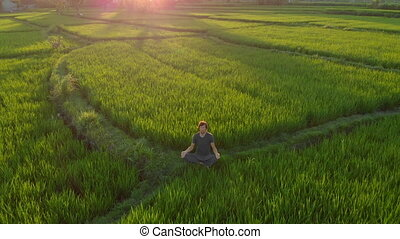Aerial shot of a man meditating on a marvelous rice field during sunrise-sunset