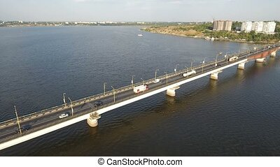 An astonishing bird`s eye view of a long modern bridge over the Southern Bug with a lot of moving cars and trucks on a sunny day in summer. The skyscape is light blue and beautiful