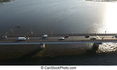 An exciting bird`s eye view of a long modern bridge over the Southern Bug with a lot of moving cars and trucks on a sunny day in summer. The drone is shooting the bridge in profile.