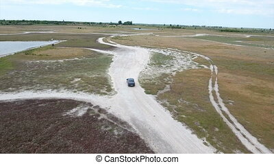 Aerial shot of a modern car driving along some sand road in...