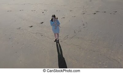 Aerial shot of a mother and baby on a beach. Cinematic 4K...