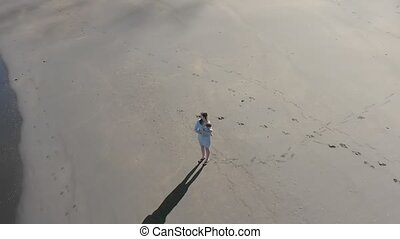 Aerial shot of a mother and baby on a beach.