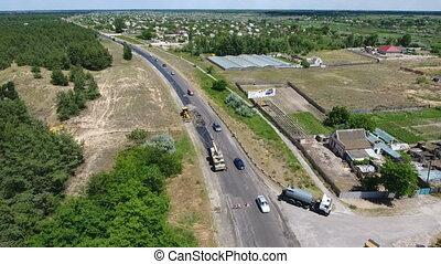Aerial shot of a motorway blacktopping, excavating, and repairing in summer