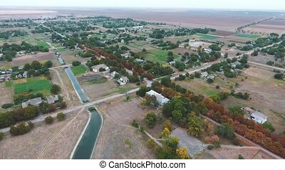 Aerial shot of a narrow canal and a straight highway going...