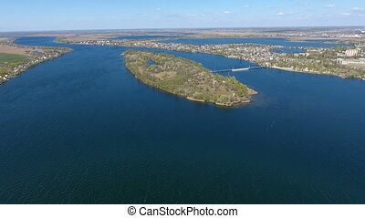 Aerial shot of a nice islet in the waters of the Dnipro river in a sunny day