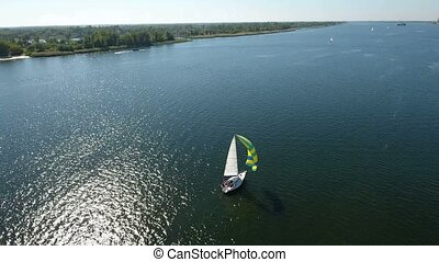 Aerial shot of a nice white yacht with two sails, one mast floating slowly