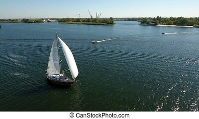 Aerial shot of a one mast white yacht and two motorboats in the Dnipro in summer