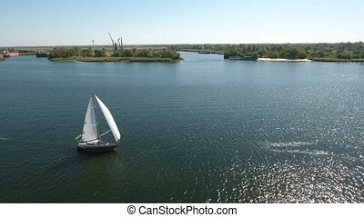 Aerial shot of a one mast white yacht sailing along the Dnipro in summer