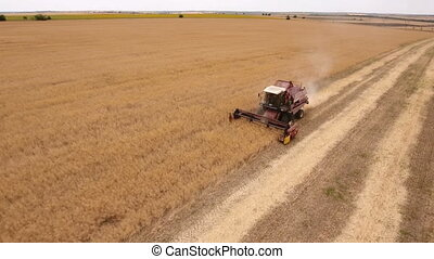 Aerial shot of a picturesque golden field and a combine...