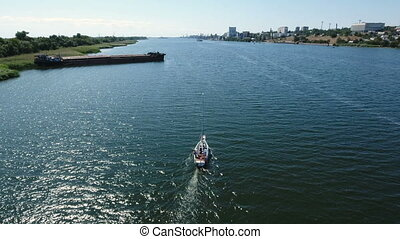 Aerial shot of a quickly moving yacht in the Southern Bug on a sunny day