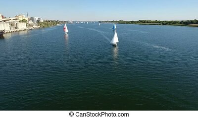 Aerial shot of a regatta from several yachts in the Dnipro river in summer