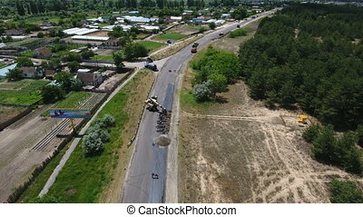 Aerial shot of a road blacktopping, excavating, and...