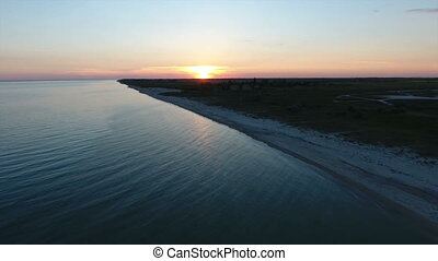Aerial shot of a romantic sunset over a  small island in the Black Sea in summer