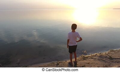 Aerial shot of a schoolboy standing on a cliff and looking at the Black Sea