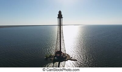 Aerial shot of a sky-high lighthouse at a spakling sunset in...